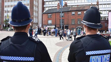Two policemen watch the anti-vax protest from a distance.