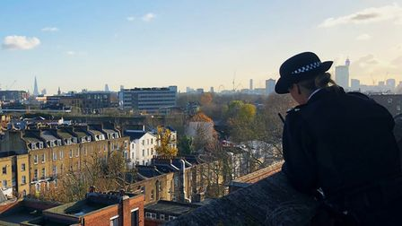 Police woman looks down at city street.