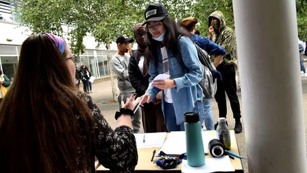 Students collect their GCSE results from tables in the courtyard at Haverstock School