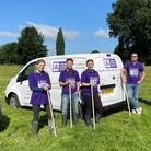 A group of five people - four in Saffron Building Society gear - hold rakes in front of a van