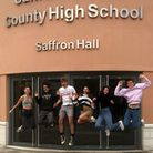 Group of students leaping in air with delight at GCSE results. Saffron Walden County High School, Essex