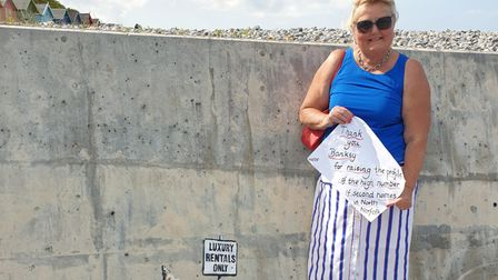 Liz Withington next to the street art on Cromer's each beach, which may or may not be by Banksy.