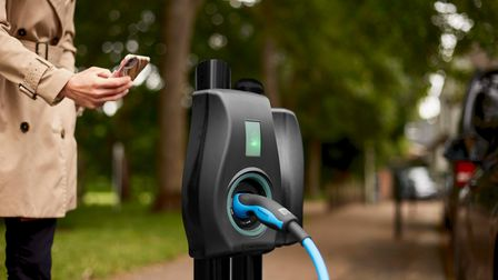 A woman uses an app to schedule charging for her electric vehicle.