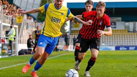 Gabby Rogers of Torquay United battles for the ball with Aaron Roberts of AFC Bournemouth U23s durin