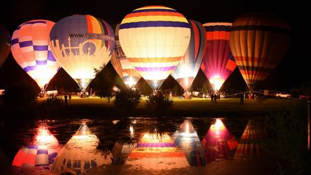 Hot air balloons are lit up as they take part in the night glow in the Old Buckenham Country Park Ba