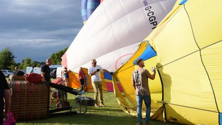 The hot air balloons are slowly inflated as they take part in the Old Buckenham Country Park Balloon
