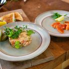 Two white plates on a wooden table, one with potted cold-smoked trout on and one with simple cold-smoked trout on
