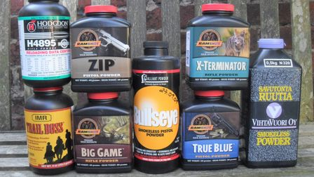 A selection of reloading powders arranged on a bench