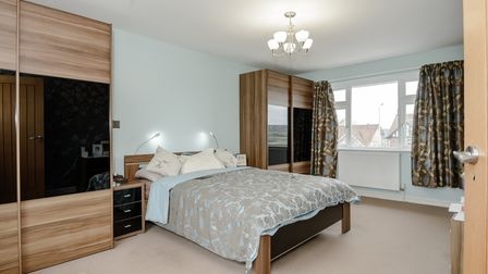 bedroom with grey walls, beige carpet, double bed with dark wooden wardrobes either side, black bedside cabinet and window