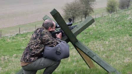 A man using crossed wooden posts as a rest while shooting long range rifle