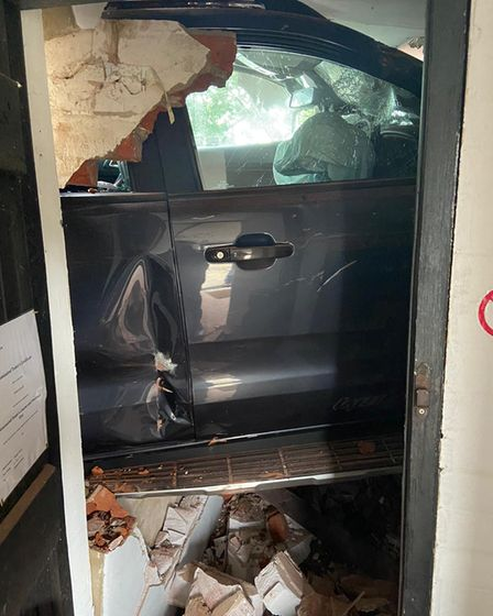 A vehicle embedded through a doorway.