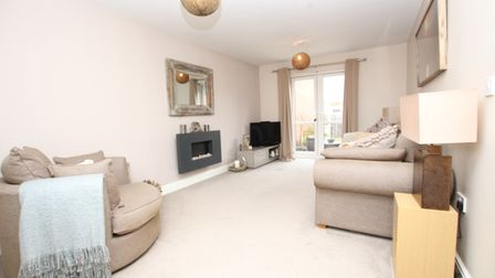 Sitting room in the house in Birkbeck Chase, West Wick, Weston, has beige carpets and sofas with French doors and fireplace