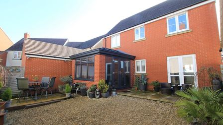 Back of the brick house in Birkbeck Chase, Weston, with a garden room added on and two patios and chippings in the garden