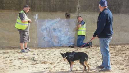 Graffiti by Banksy on North Beach in Lowestoft being covered up after being defaced with whute paint