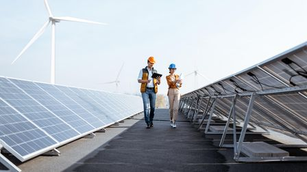 Two workers inspecting solar panels on a roof.