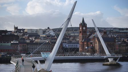 The Peace Bridge crosses the River Foyle in sight of The Guildhall building in Londonderry, Northern