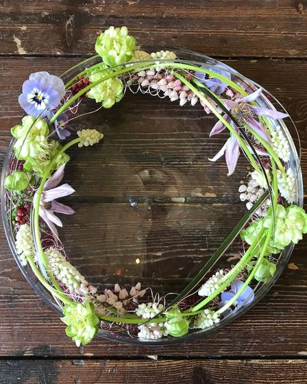 A wreath of greenery and blue flowers on a dark wood coffee table