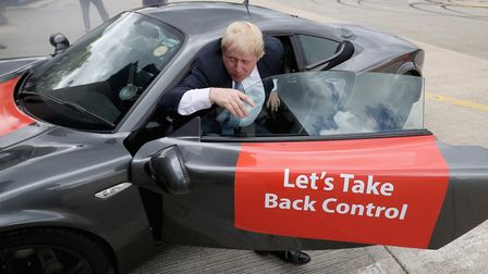 Boris Johnson MP emerges from a sports car after it performed 'donuts' during a visit to Ginetta Spo