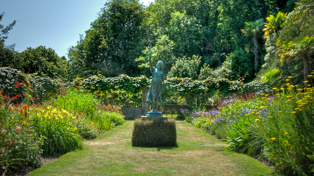 A border of colourful flowers surround a statue of a woman holding one arm up