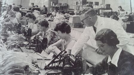 In the machine room workers stitch the upper parts of the handbags together.