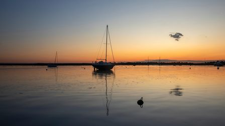 Reflections of boats against the sunset at Old Leigh, Leigh-on-Sea, Essex, England