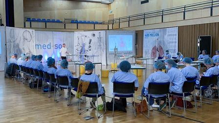 Students in Saffron Hall, Saffron Walden, Essex, at the Med-Soc event, wearing blue hairnets and white coats