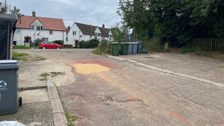 Paint spilt on the floor at the entrance to the private road where the shed is located.