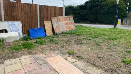 A sign next to the shed advertising a second hand sale