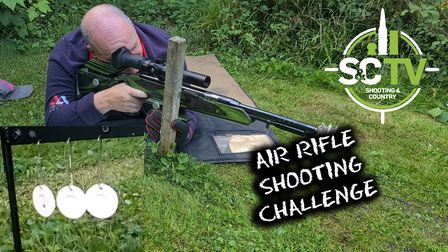 A man lying on grass shooting an air rifle, with a target shown picture-in-picture