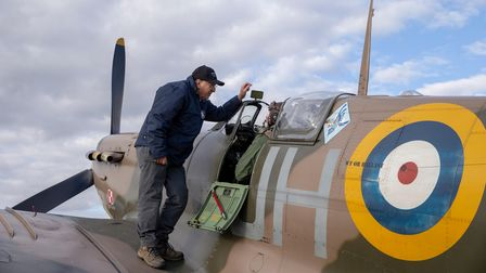A crew member helps a Spitfire pilot before taking off.