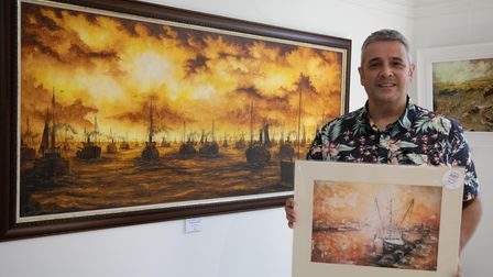 Artist Lorenzo Barron with his painting of steam drifters returning to port, on display at the Ferini Gallery in Pakefield.