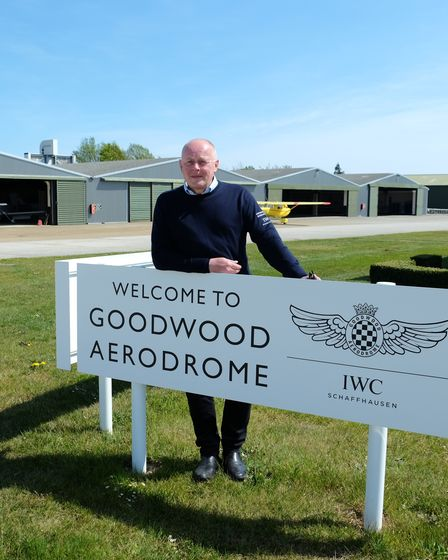 Aerodrome Manager Mark Gibb standing by the sign at Goodwood Aerodrome