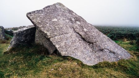 A stone slab lies on a diagonal resting on more slabs to make a small chamber