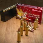 Hornady Superformance Varmint ammunition box on a table with a loaded magazine to the left, and loose rounds in foreground