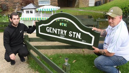 Glenn Ryan, right, and his future son-in-law, Aaron Smith, with a railway sign they have made in the