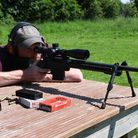 Rifle reviewer Chris Parkin shooting the Howa 1500 Carbon 6.5 Creedmoor in MDT XRS Chassis from a bench in a field