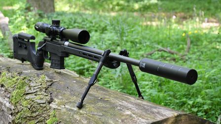 The Howa 1500 Carbon 6.5 Creedmoor in MDT XRS Chassis with Tier-One Evolution bipod, balanced on a log in woodland