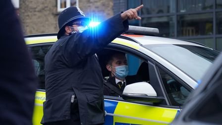 A policeman points to something.