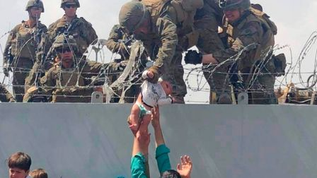A baby being lifted across a wall at Kabul Airport in Afghanistan by US soldiers.