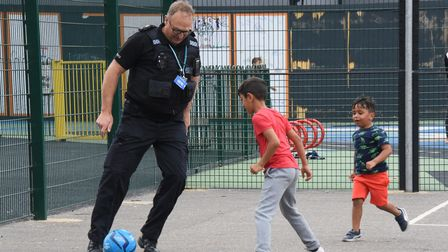 PC Mike Small plays football with local children during the community action day at Maple Park in Ip