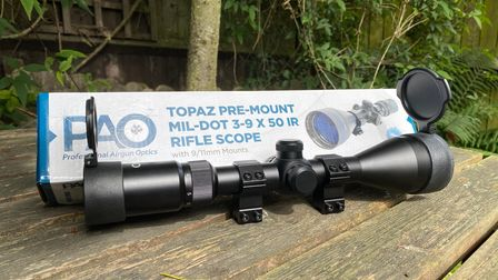 The PAO Topaz pre-mount rifle scope in front of its packaging on a wooden table