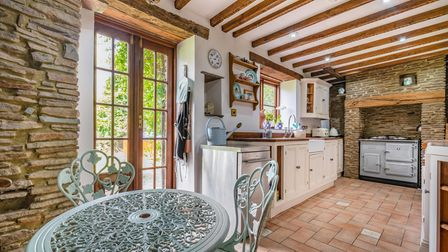 Kitchen-breakfast room in the cottage in St Marys Grove, Nailsea, with cream units, French doors, ceiling beams and an Aga