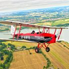 A man flying in a red Tiger Moth G-ANTE