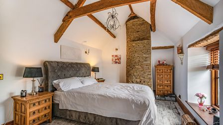 double bedroom in the cottage in St Marys Grove Nailsea with bed, drawers, window, ceiling beams and stone chimney breast