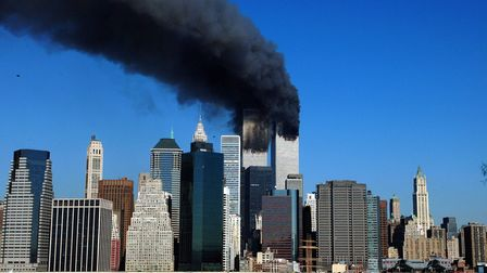 The twin towers of the World Trade Center billow smoke after hijacked airliners crashed into them on 9/11