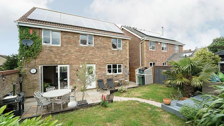 Back of the house in Bluebell Road, Wick St Lawrence with lawned garden, patio with table and chairs, plants and barbecue