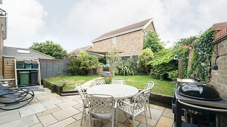 Back garden in the house in Bluebell Road, Wick St Lawrence, with patio and furniture, a barbecue, lawn behind and bin store