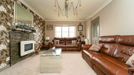 sitting room has beige carpet, clear coffee table, brown leather sofa and wall-mounted fire,with slate surround