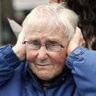 An onlooker reacts to loud dance music by putting her hands over her ears as members of Dublin's gay