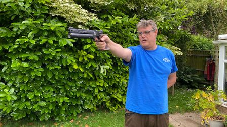 Dave Barham shooting the Reximex Mito air pistol in a garden, against a hedge